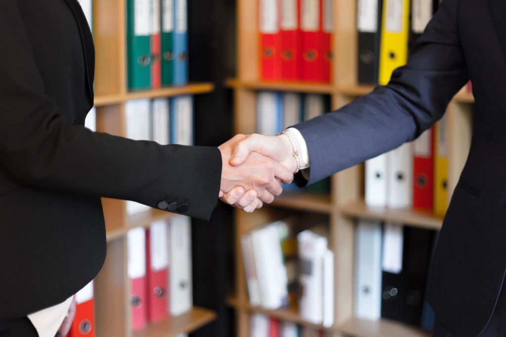 Handshake in front of folders
